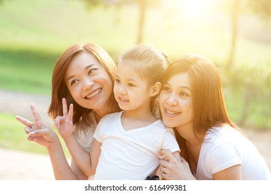 Asian family portrait at nature park, morning outdoor with sun flare.