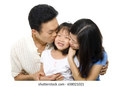 Asian family portrait on white background. Asian parents kissing daughter.