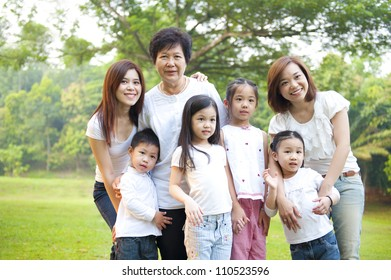 Asian family portrait at outdoor park, 3 generations.