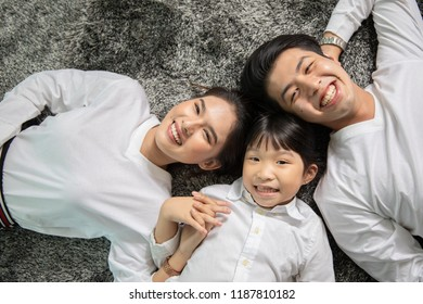 Asian family portrait top view of cute little girl and her beautiful young parents looking at camera with happy people smiling in Home ,Lifestyle and Holiday Concept.