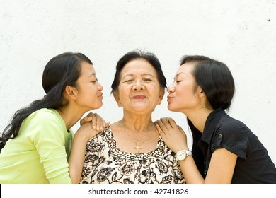 asian family portrait of two teen girls show their love to their old grandmother