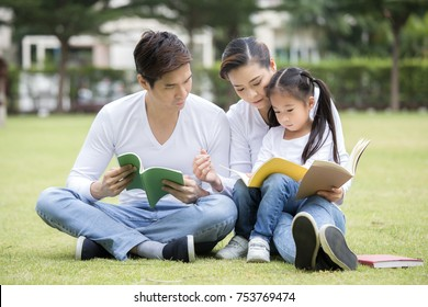 Asian family reading book together at outdoor place. People lifestyle concept.