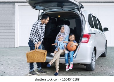 Asian family ready for vacation while holding a picnic basket into the car. Shot in the house garage