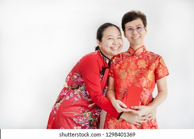 Asian family in red colour Chinese traditional dress holding red packet money at home,Happy Chinese New Year concept