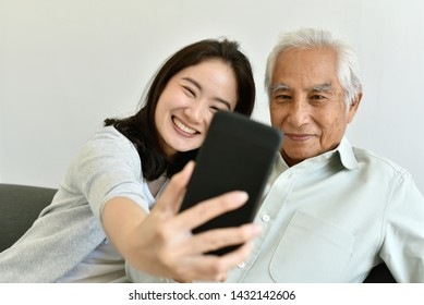 Asian family relationship, Daughter and elderly father using smartphone for selfie together, Senior people spend time learning to use social media and digital technology platform.