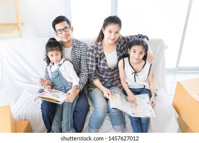 asian family relax and sitting near sofa, they moving to new resident, they plan to choose color of interior home and home decoration, they looking color catalog, they feeling happy in family time