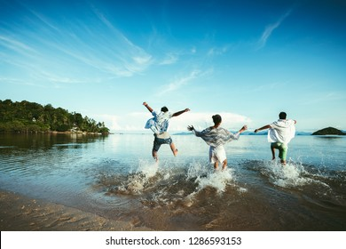Asian family running on background of sunset beach and sea