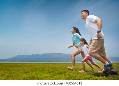 Asian family running on open grasslands.