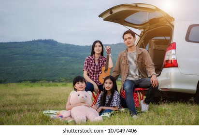 asian family sitting in the car for a trip and summer vacation in camper van