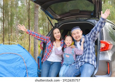 Asian family sitting in car trunk going camp on vacations . Family travel by car.