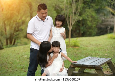 asian family sitting on the bench park