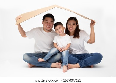Asian family smiling and playing house by brown paper on isolated white background. New home young family concept