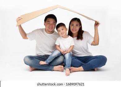 Asiatische Familie lächelt und spielt Haus auf braunem Papier auf isoliertem weißem Hintergrund. Neuer Familienbegriff