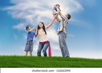 Asian family spending a fun summer day in meadow