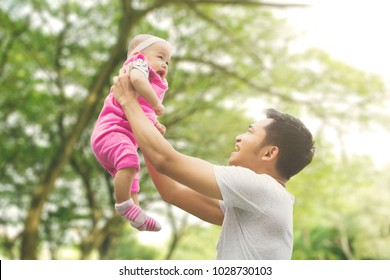 Asian family spending spring concept: a father lifting daughter with blur tree background