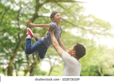 Asian family spending spring concept: a father lifting son with blur tree background