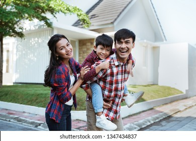 asian family standing in front of their new house together. mother father and son new home