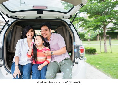 Asian family summer activity. Father ,mother and daughter sitting back of car for travel in the outdoor.
