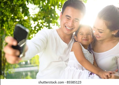 Asian Family Taking Photographs in the park