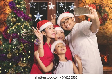 Asian family taking a selfie photo by using a smartphone while celebrating Christmas in the living room