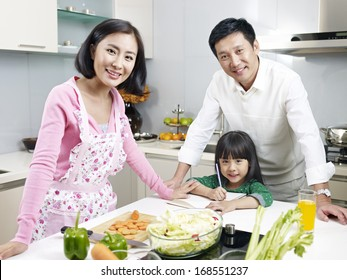 asian family of three smiling in kitchen, focus on father and child.