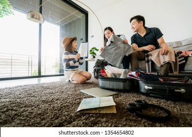Asian Family travel concept happiness dad mom daughter packing stuff and planing for vacation trip with exited and joyful