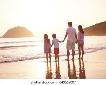 asian family with two children enjoying sunrise on beach.