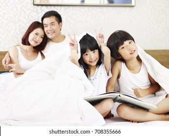 asian family with two children having fun in bed.