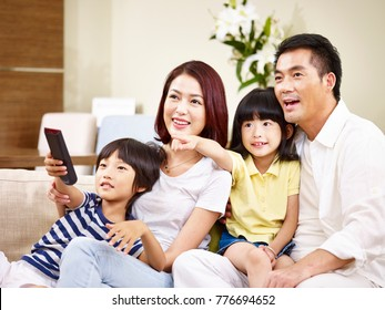 asian family with two children sitting on couch at home watching TV.