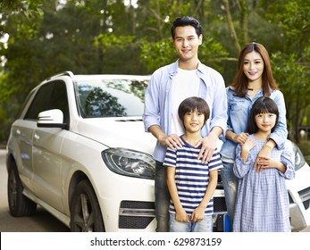 asian family with two children taking a photo during travel by car.