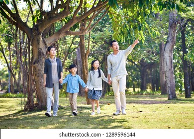 asian family with two children walking hand in hand outdoors in park.