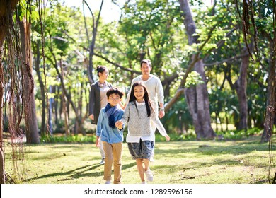 asian family with two children walking relaxing having fun in park happy and smiling.