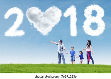 Asian family walking in the meadow while pointing at clouds shaped numbers 2018 and heart