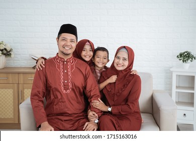 Asian family wearing Malay traditional clothes sitting on the sofa with the concept of Eid Mubarak