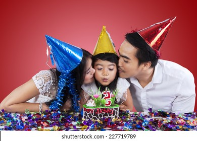Asian family wearing party hats while celebrate little girl birthday