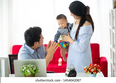 Asian family working at home. Busy parents doing their business and takecare baby together at house.