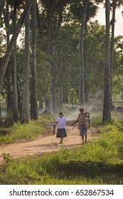 Asian farmer carrying bamboo cylinder and walking with his granddaughter back home together.
