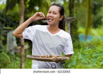 asian farmer woman eating fried grasshoppers