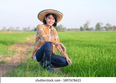 Asian farmer woman sitting and looking camera at farm