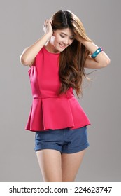 Asian Fashion Model in Leatherette Red Drop-Waist Crepe Top with light blue denim shorts.