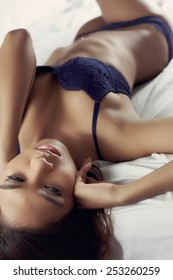Asian fashion model in lingerie in desire on the white sheet