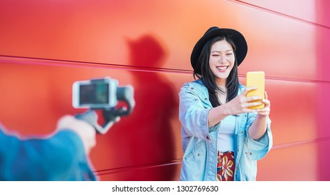 Asian fashion woman vlogging and using mobile smart phone outdoor - Happy Chinese trendy girl having fun making video with gimbal camera - Millennial people, Generation z and technology concept
