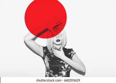 Asian fashion woman in wig hide from hot red sun. Beautiful japanese geisha sakura blossom clothes against red sun asia concept design.