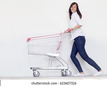 asian fashionist teen girl have funny action with shopping cart in love shopaholic concept