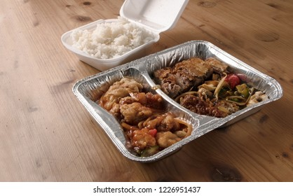 asian fast food from delivery service in a foil container and rice in a foam box on a wooden table, copy space, selected focus