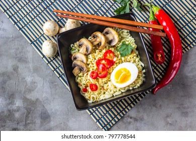 Asian fast food: Japanese noodles soup ramen with egg, mushrooms and red hot peppers on concrete background. Selective focus