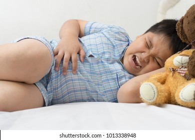 asian fat boy suffering from stomachache indicating location of pain