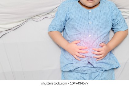 asian fat child suffering from stomachache and red spot indicating location of pain. healthy concept