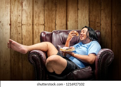Asian fat man eating donuts on plate in the sofa. Fat man diet concept