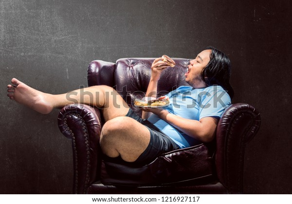 Asian fat man snacking donuts on the couch at home